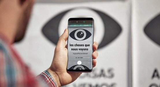 Kuva henkilöstä pitämässä Galaxy S9+ -puhelinta, jonka näytöllä näkyy käännetty kyltti ja taustalla on kyltin kuva kääntämättömänä