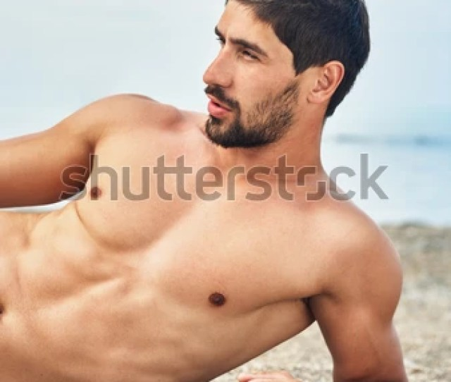 Muscular Handsome Young Man With Naked Torso Lying On The Beach Sea Background