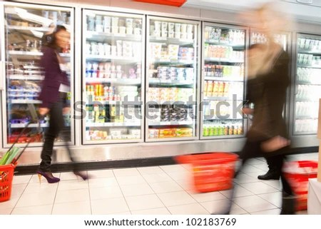 Blurred motion of people walking near refrigerator in shopping centre with baskets - stock photo