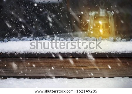Oil Lamp on the Wooden Window and Falling Snow  - stock photo