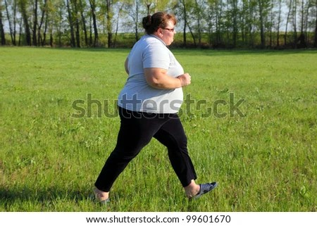 stock photo : sport - overweight woman running on green meadow