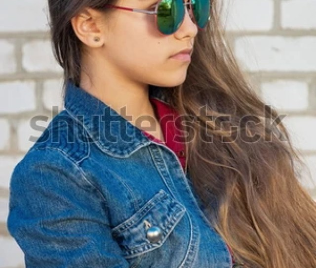 Portrait Of Fashionable Teen Girl With Long Hair On A Background Of A Brick Wall