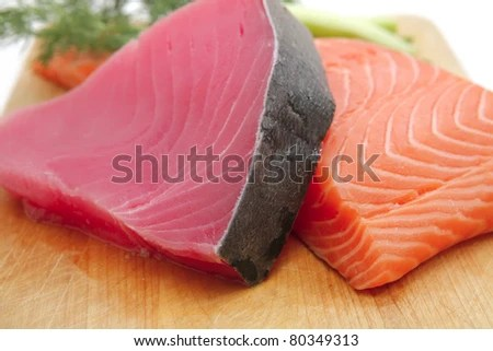 stock photo : fresh raw salmon and tuna fish  pieces on wooden plate isolated on white background