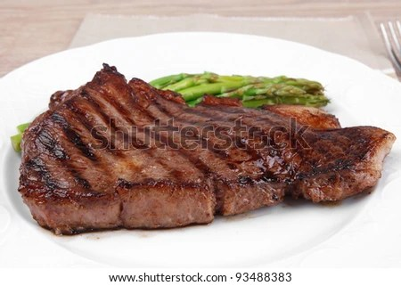 stock photo : meat table : rare medium roast beef fillet with asparagus served on white plate with cutlery over wooden table
