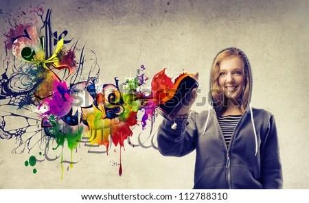 Beautiful blonde girl making a graffiti - stock photo