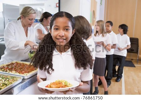 Students in cafeteria line with one holding up her healthy meal looking at camera - stock photo
