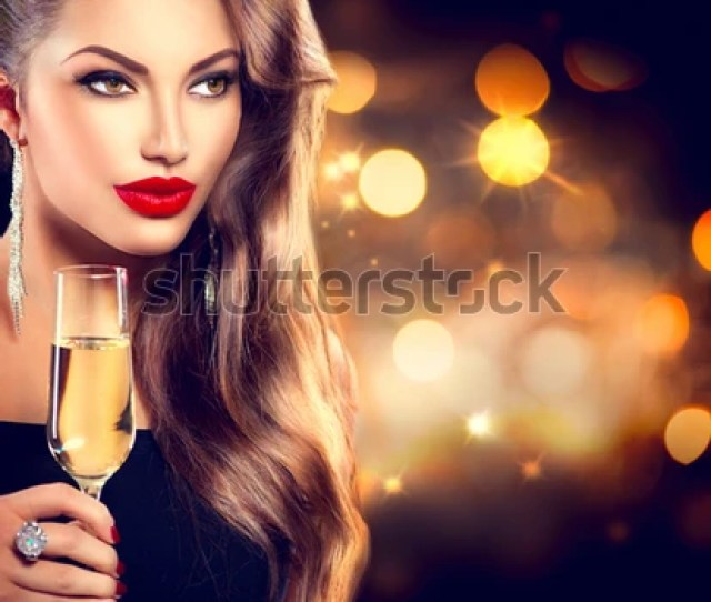 Sexy Model Girl With Glass Of Champagne At Party Drinking Champagne Over Holiday Glowing Background