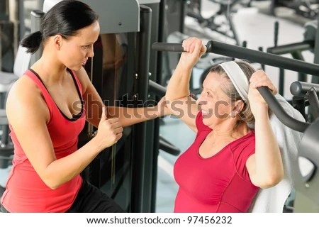 stock photo : Personal trainer assist senior woman exercising on machine at gym