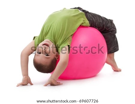 Little boy doing gymnastic exercises with a large rubber ball - stock photo