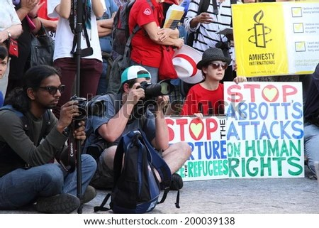 BRISBANE, AUSTRALIA - JUNE 22 : Unidentified protester holding anti government immigration policy sign whilst attending World Refugee Rally June 22, 2014 in Brisbane, Australia