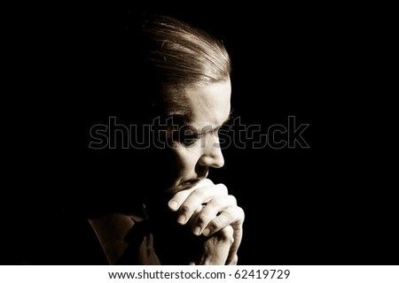 Head and hands of praying man, low-key portrait - stock photo