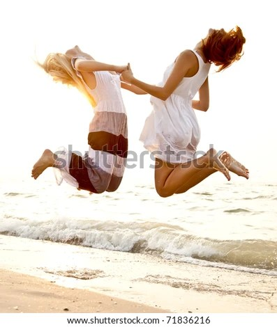 stock photo : Two beautiful young girlfriends jumping on the beach at sunset. Photo with counter-light on background.