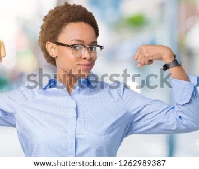 Young Beautiful African American Business Woman Over Isolated Background Showing Arms Muscles Smiling Proud Fitness