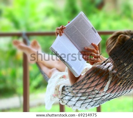 stock photo : Young woman reading a book lying in hammock