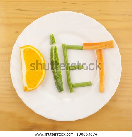 stock photo : on varnished wooden table is a white plate with laid out on her word - diet - composed of slices of different fruits and vegetables