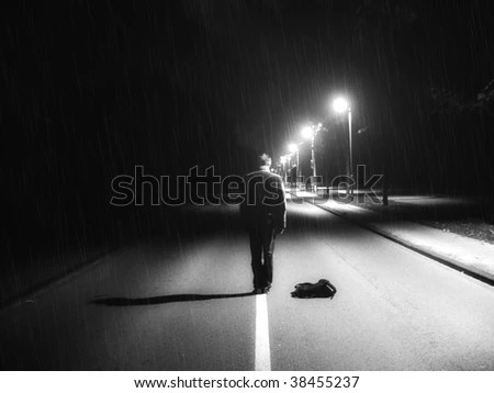 Lonely guy in darkness on the middle of road - stock photo