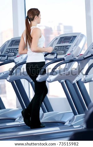 stock photo : Young woman at the gym exercising. Run on on a machine.
