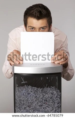 Young caucasian businessman shredding documents - stock photo