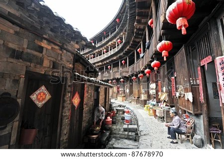 ZHANGZHOU - SEPTEMBER 27: Hakka people settle in Tulou building on September 27 2010, in Zhangzhou, China. The Hakka people arrived from Central China to settle in Zhangzhou after centuries of war. - stock photo