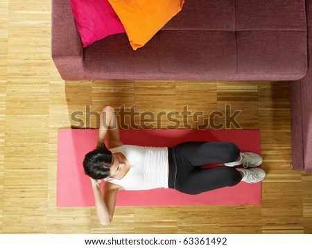 stock photo : mid adult woman training abdominals at home. Horizontal shape, full length, high angle view, copy space