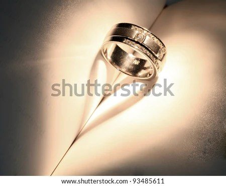 "stock photo : Wedding Luxury Diamond ring casting a heart on Book Using for ""Love never ends"" Concept in Valentine Holiday"