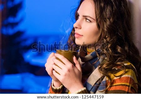 Dreamy thoughtful beautiful brunette with mug of hot beverage. - stock photo