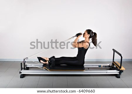 stock photo : Bicep reformer position. Pilates gymnastics is a Germanic evolution of yoga, used by athletes to improve flexibility and body fitness and by chiropractors for patient recovery.