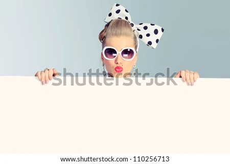 Beautiful young woman with pin-up make-up and hairstyle posing in studio with white board. - stock photo