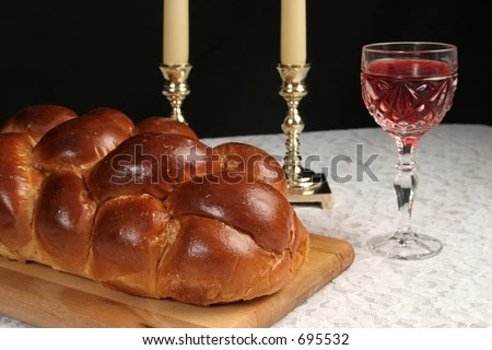 A table set for Shabbat with challah bread, candlesticks and wine.  Black background. - stock photo