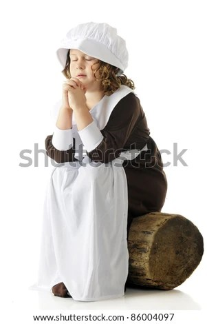 An elementary-aged Pilgrim girl sitting on an old log with her eyes closed and hands folded in prayer.  On a white background. - stock photo