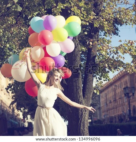 Happy young woman with colorful latex balloons, outdoor - stock photo