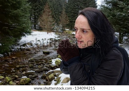 woman looking concerned / cold by stream in snow covered forest in winter - stock photo