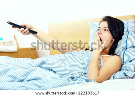 woman watching tv in the morning - stock photo