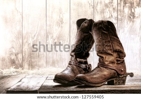 American West rodeo pair of traditional leather roper style western riding slouch cowboy boots with authentic ranching spurs on wood deck in front of an old ranch wood barn - stock photo