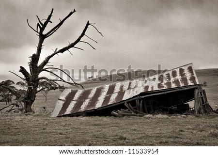 an old farm bulding lays decaying in the field - stock photo