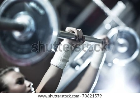 stock photo : Young woman weight training. Focus on hand.