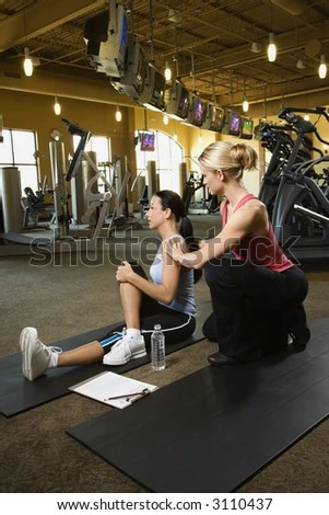 stock photo : Prime adult Caucasian female with personal trainer at gym.