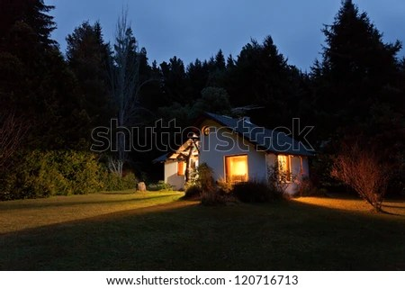 House in the forest at night - stock photo