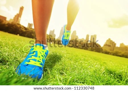 Runner - running shoes closeup of woman barefoot running shoes. Female jogging in Central Park, New York City. - stock photo