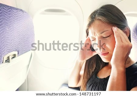 Fear of flying woman in plane airsick with stress headache and motion sickness or airsickness. Person in airplane with aerophobia scared of flying being afraid while sitting in airplane seat. - stock photo
