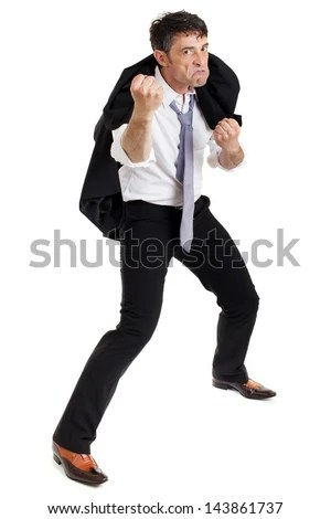 Belligerent angry man picking a fight standing with his jacket over his shoulder and legs apart scowling and threatening with his fist - stock photo