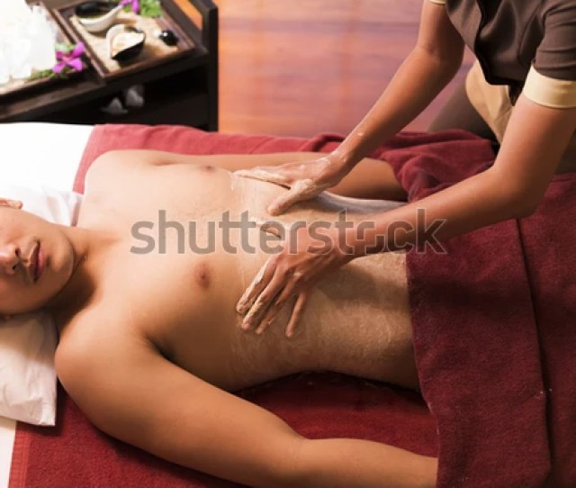 Asian Man Getting Massage And Body Scrub In Spa