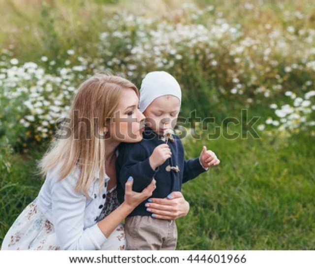 Charming Blonde Mom Blows With His Young Son On A Dandelion