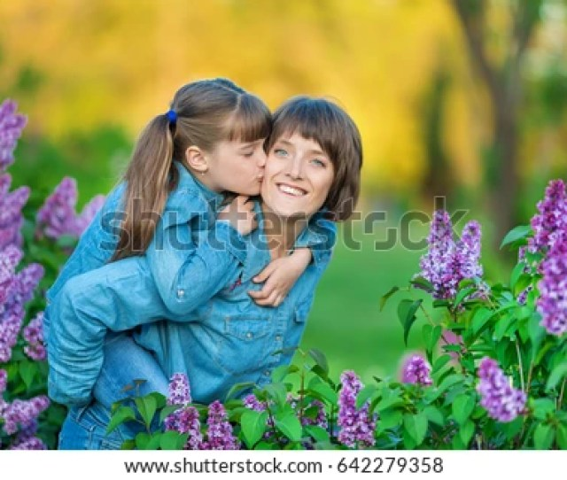 Cute Adorable Beautiful Mother Lady Mom Woman With Brunette Girl Daughter In Meadow Of Lilac Purple