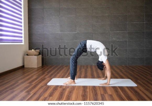 Experienced yogi doing wheel yoga pose in gym. Man practicing yoga. Yogi concept. Side view.