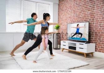 Una familia apropiada haciendo ejercicio de fitness en línea de Stretching de yoga