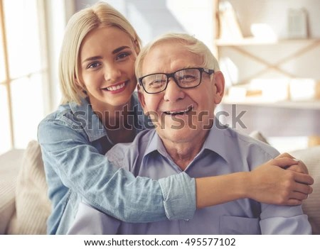 Handsome Old Man And Beautiful Young Girl Are Hugging Looking At Camera And Smiling While