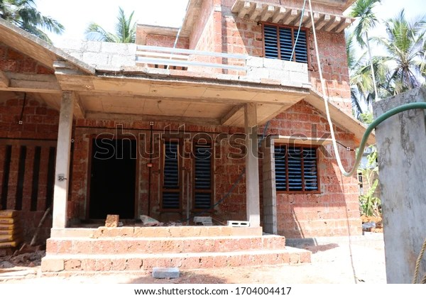 Kerala home construction structure site, home building progress with natural bricks chenkallu and concrete