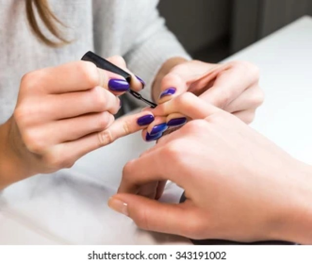 Manicurist Putting Black Shellac On The Fingernails Of A Lady Client In A Beauty Salon With