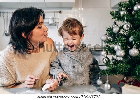 Mom Blows Her Son On The Background Of The Christmas Tree The Child Having Fun